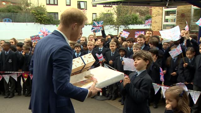 Exterior shots showing Prince Harry Duke of Sussex accepting gifts from students after his visit to St Vincent's Catholic Primary School on March 20...