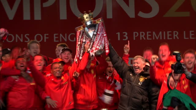 """exterior shots sir alex ferguson & manchester united players lift premier league trophy & dance around on stage whilst singing along to queen - """"we... - trophy stock videos & royalty-free footage"""