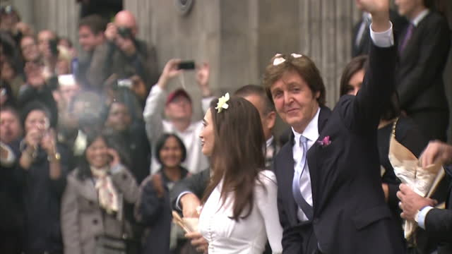 exterior shots sir paul mccartney & nancy shevell walk out from marylebone town hall to a shower of rose petals being thrown by family & friends.... - celebrities video stock e b–roll