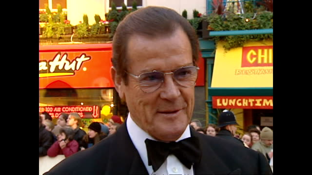 exterior shots sir roger moore, actor, and partner louisa mattoli on red carpet at the bafta awards, posing for photographs, and talking about his... - 俳優 ロジャー・ムーア点の映像素材/bロール