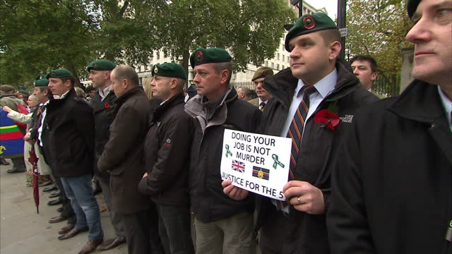 "exterior shots small crowd of marines stood in protest outside the dates of downing street with banner being held ""doing your job is not murder"".... - royal marines stock videos & royalty-free footage"