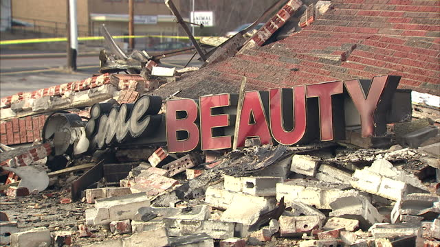 exterior shots smoke rising from rubble across road with cars driving in foreground rubble from dime beauty shop on ground with sign amongst debris - dime stock videos and b-roll footage