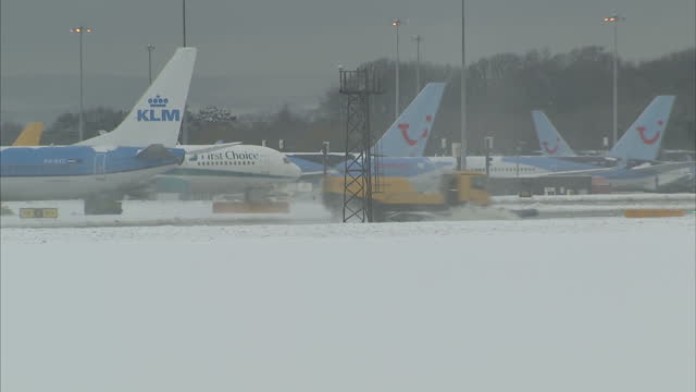 Exterior shots snow ploughs clearing runway and planes stranded at terminal
