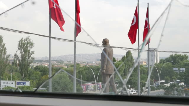 Exterior shots statue of Mustafa Kemal Ataturk and Turkish flags blowing in wind seen through broken glass window of the Ankara Police Department...