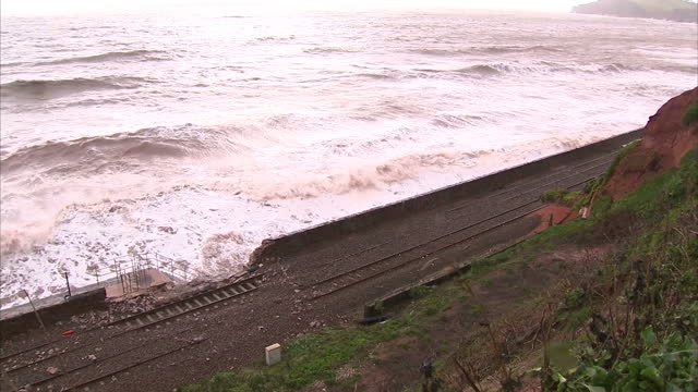 vidéos et rushes de exterior shots storm waves crashing against coastal rail tracks, damaging walls and moving debris onto the rail lines. on in devon, england. - érodé