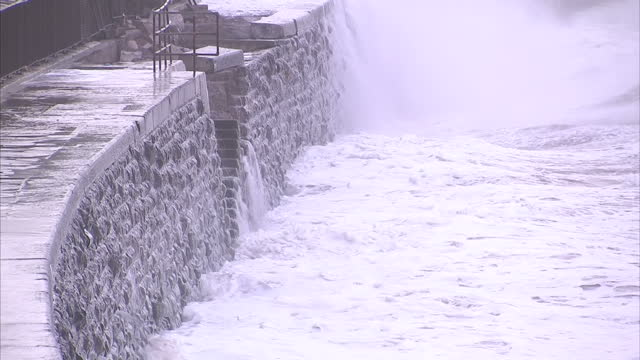 vidéos et rushes de exterior shots storm waves crashing against coastal railway line on seafront with dalwish station in the background. on in devon, england. - érodé