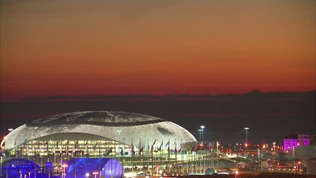 vídeos y material grabado en eventos de stock de exterior shots sunset over the bolshoy ice dome at the sochi winter olympic park with passenger plane flying overhead on in sochi russia - sochi