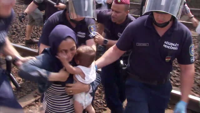 exterior shots syrian refugee throws his family wife and baby onto tracks in protest to migrant camps in bicske, riot hungarian police arresting... - ハンガリー文化点の映像素材/bロール