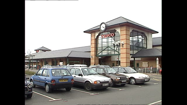 exterior shots tesco supermarket with shooper entering store cars parked in the car park and 'now open' signage outside on april 10 1995 in london... - tesco点の映像素材/bロール