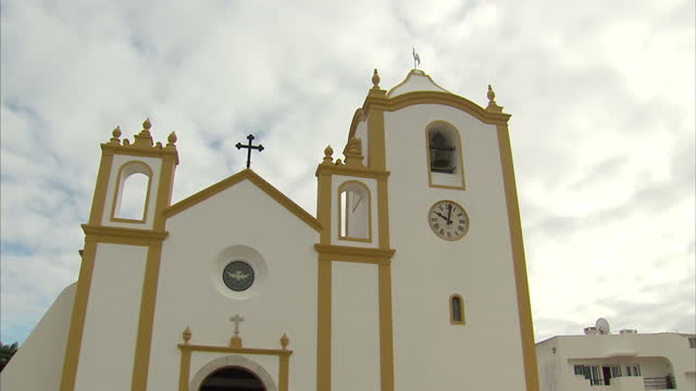 exterior shots the church of nossa senhora da luz praia da luz portugal includes shots of weathercock atop church and people queueing up for holy... - praia stock videos & royalty-free footage