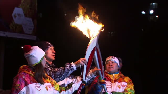 exterior shots the olympic torch being carried through murmansk, russia. with handover between two torch bearers and photo op before continuing on... - flaming torch stock videos & royalty-free footage