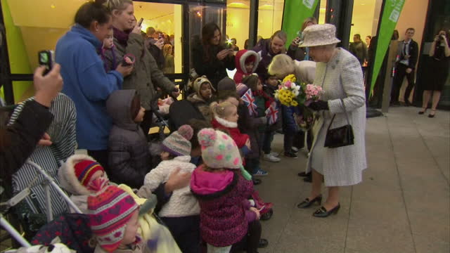 vídeos de stock, filmes e b-roll de exterior shots the queen and camilla walk along line guests & receive flowers from children. the queen and camilla depart barnados offices on... - ilford