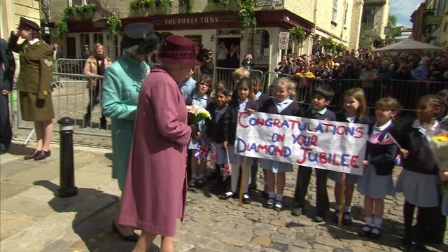 exterior shots the queen greets school children waving union flags during her diamond jubilee tour of windsor. interior shots the queen meets various... - diamantenes jubiläum stock-videos und b-roll-filmmaterial
