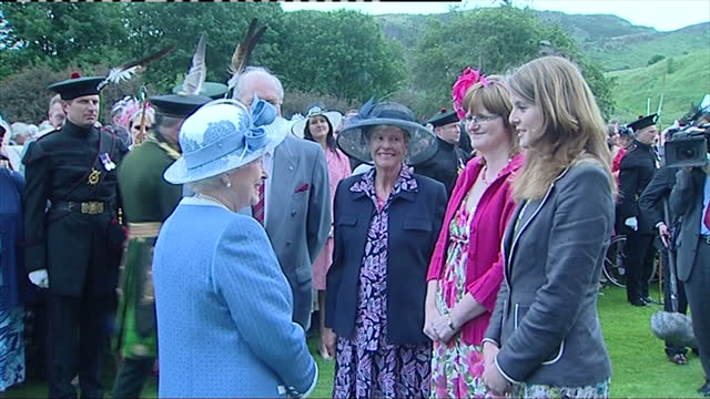 vidéos et rushes de exterior shots the queen in turquiose outfit prince philip duke of edinburgh who wears top hat tails greet guests at a garden party in holyrood queen... - couvre chef