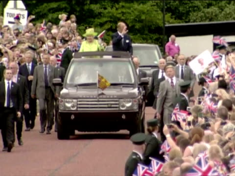 exterior shots the queen prince philip travel in open top range rover waving to large crowds of well wishers as they arrive in stormont queen... - ストーモント点の映像素材/bロール