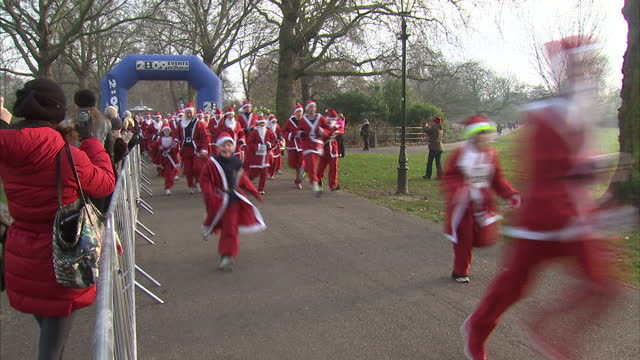 Exterior shots thousands of runners dressed up as Santa Clause run through Battersea Park in a six kilometer training run as part of a money raising...