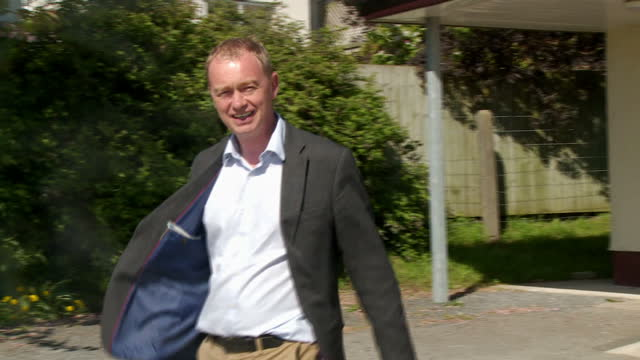 exterior shots tim farron leader of the liberal democrats walking in to polling station to vote in the local elections in allithwaite in his... - politische gruppe stock-videos und b-roll-filmmaterial