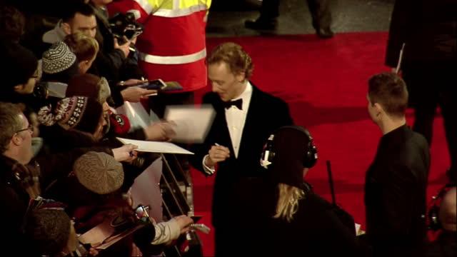 vídeos de stock e filmes b-roll de exterior shots tom hiddleston signs autographs for fans the red carpet at the bafta awards arrivals tom hiddleston on the bafta red carpet on... - autografar