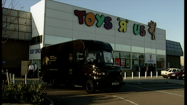 exterior shots toys r us staff unloading boxes of teletubbies toys out of back of van and take them into store. teletubbies christmas craze 1997. on... - negozio di giocattoli video stock e b–roll
