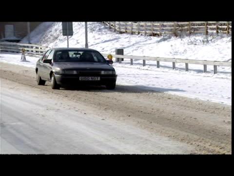 exterior shots traffic on m11 / exterior shots slippery surface signs. exterior shots police patrol, snowplough & road recovery trucks on snow-bound... - エセックス州点の映像素材/bロール