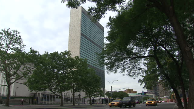 exterior shots united nations un building headquarters in new york with un signage flags outside exterior shot street signs for united nations plaza... - united nations stock videos & royalty-free footage