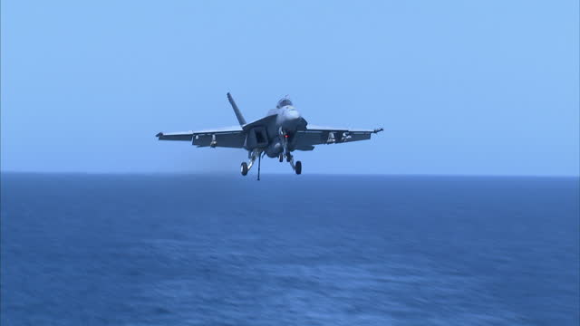 exterior shots us navy f/a18e super hornet jets landing on flight deck of us navy uss dwight d eisenhower aircraft carrier and conducting flypasts on... - united states navy stock-videos und b-roll-filmmaterial