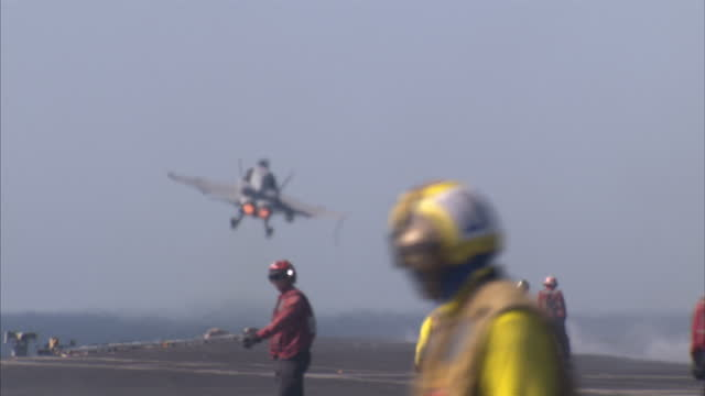 exterior shots us navy flight deck crew preparing and releasing f/a18e super hornet jets for take off from flight deck of us navy uss dwight d... - 海軍点の映像素材/bロール