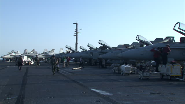 exterior shots us navy flight deck crew preparing fighter jets and loading weapons ahead of training exercise on flight deck of us navy uss dwight d... - 海軍点の映像素材/bロール