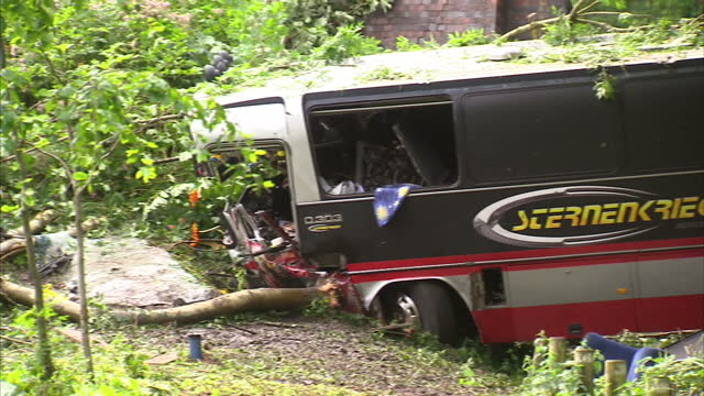 exterior shots us rock band baroness' crashed tour bus lying at the bottom of steep verge. exterior shots crashed bus showing debris & smashed cab... - baroness stock videos & royalty-free footage