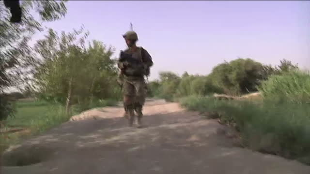 exterior shots us troops walk singlefile through fields farmland exterior shots us marines walk inside mud walled compound along with afghan soldiers... - afghanistan video stock e b–roll