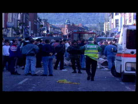vidéos et rushes de exterior shots var of bomb aftermath - fire engines, ambulances, police & crowds at scene. exteriors var of civilians help clear area of bricks &... - var