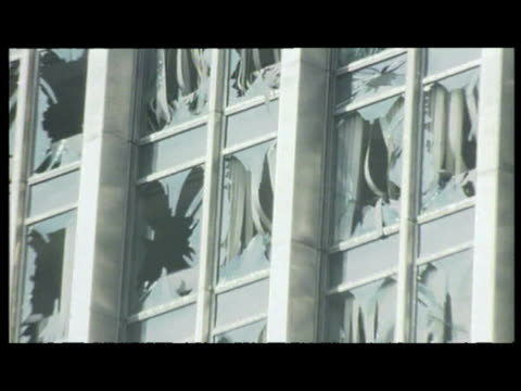 exterior shots var of bomb blast destruction; shattered glass, boarded up shops, office blocks with shattered windows. exteriors police & firemen at... - var stock-videos und b-roll-filmmaterial