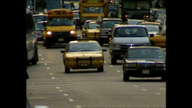 vídeos de stock e filmes b-roll de exterior shots vehicles driving along busy street, including nyc yellow taxi cabs and yellow school buses. on november 05, 1996 in new york city. - yellow taxi