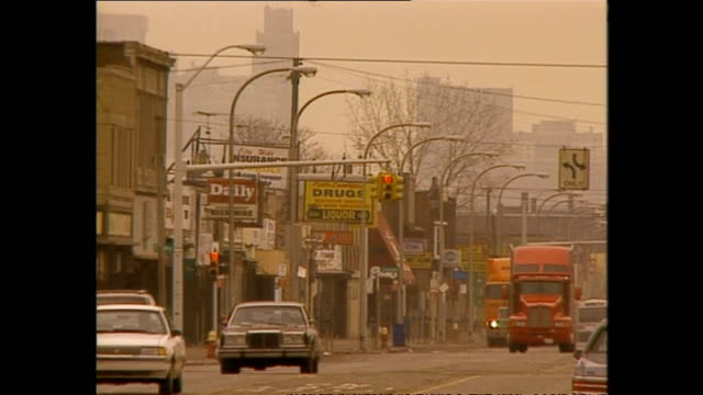 vidéos et rushes de exterior shots vehicles driving along road lined with rundown looking independent stores on march 12 1994 in detroit michigan - detroit