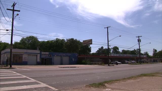 Exterior shots vehicles driving along road through Dixon Circle neighbourhood past a rundown 'Super Discount' liquor store on July 10 2016 in Dallas...