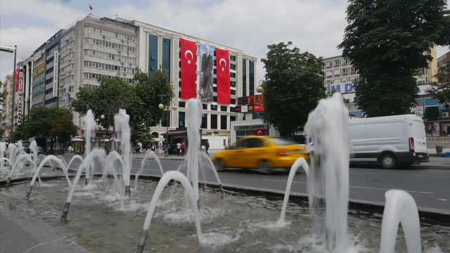 Exterior shots vehicles driving along street with large Turkish flags and banners of Mustafa Kemal Ataturk First President of Turkey hanging from...