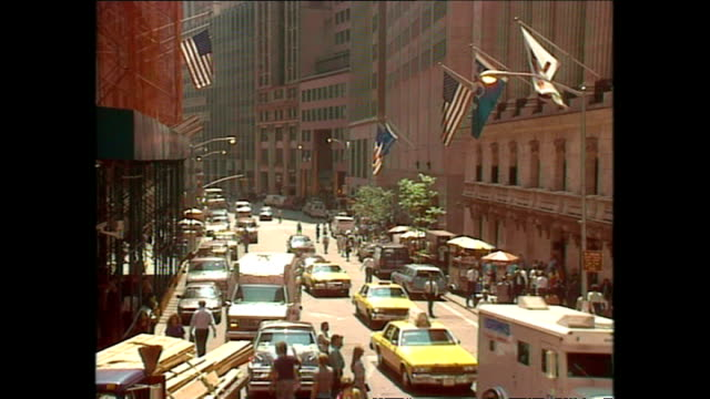 stockvideo's en b-roll-footage met exterior shots vehicles driving along wall street past the nyse with flags flying from the building on august 15 1990 in new york city - wall street lower manhattan