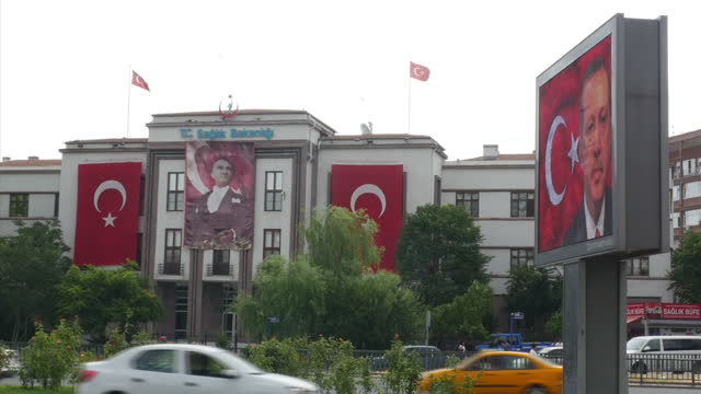 Exterior shots vehicles driving in busy street in front of the Ministry of Health building with large Turkish flags flying from building and large...