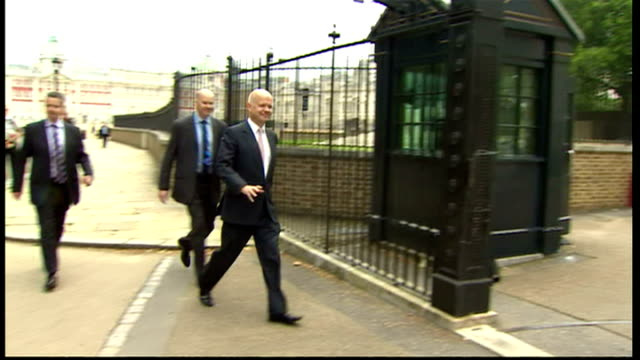 exterior shots william hague mp walk to rear entrance downing st let through by poiliceman william hague arriving for meetings on syria on august 27... - william hague stock-videos und b-roll-filmmaterial