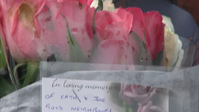 exterior shots woman places bouquet of flowers outside home of murdered couple exterior shots floral tributes with messages of sympathy floral... - midlands occidentali video stock e b–roll