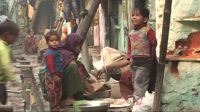 exterior shots women young children living in a slum street with open sewer running through it exterior shots group of children smile at the camera... - デリー点の映像素材/bロール