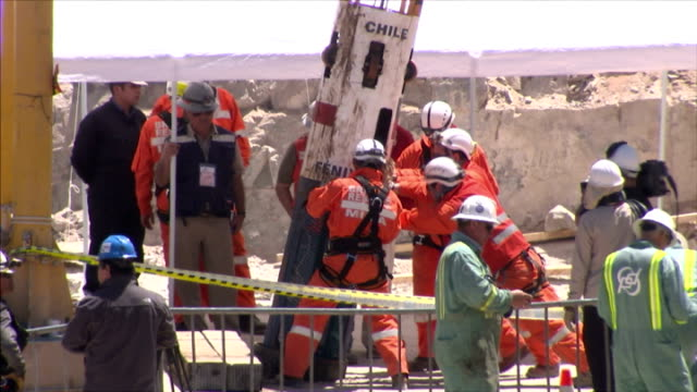 exterior shots workmen use winches and pulleys to extract chilean miners from the collapsed mine shaft at camp hope in the atacama desert and miners... - minatore video stock e b–roll