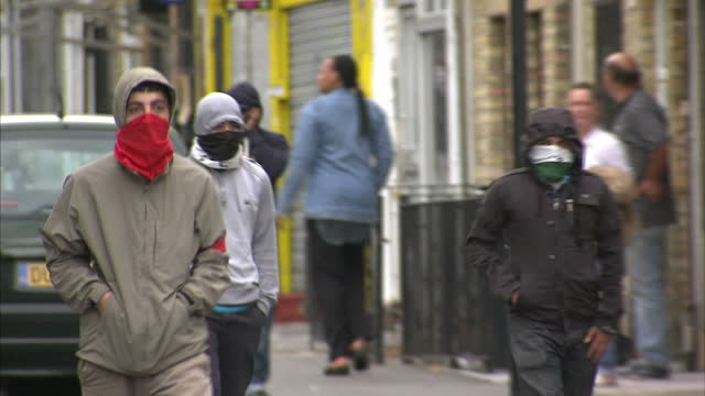 vidéos et rushes de exterior shots youths & hooded rioters gathered at one end of road with riot police standing at other end of street, general shots man facing up to &... - hackney