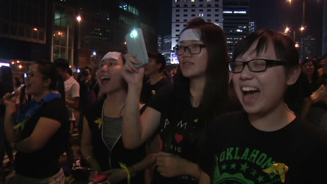 Exterior showing night time demonstration in progress walk through crowd of young people chanting in unison on September 30 2014 in Hong Kong Hong...