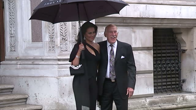 vidéos et rushes de exterior showing sir bruce forsyth posing for press with his wife and umbrella - emma freud