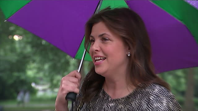 vidéos et rushes de exterior showing television presenter kirsty allsopp arrival with green and purple umbrella - emma freud
