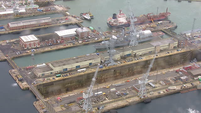 exterior shows aerials over portsmouth royal dockyard lots of industry warship in wet dock october 16 2013 in london england - 造船所の労働者点の映像素材/bロール