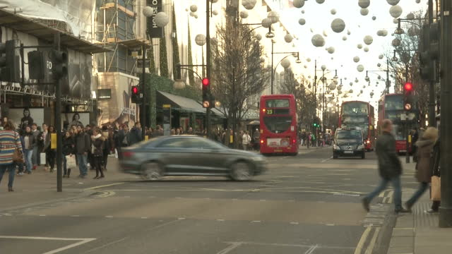 vídeos de stock e filmes b-roll de exterior shows london's oxford street with shoppers, christmas decorations, red london buses and black hackney cabs - hackney