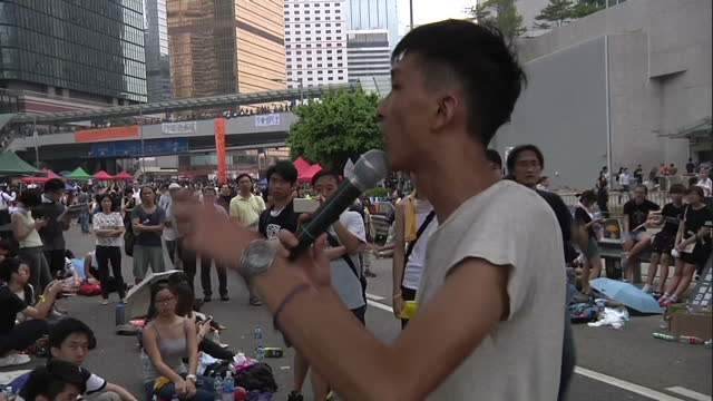 Exterior shows man with microphone addressing crowd of seated demonstrators on October 01 2014 in Hong Kong Hong Kong