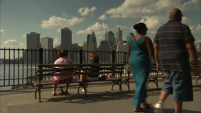 exterior shows new york syyline view from brooklyn promenade pair seated on bench admiring view over hudson river - pair stock videos & royalty-free footage